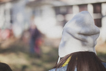 The back of a girl's head wearing a white beanie