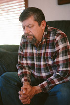 a man praying on a couch