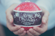 a large red ornament with the words Merry Christmas being held in someone's hands