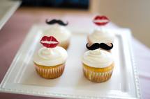 Cupcakes topped with lips and mustaches.