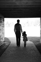 A man and child walk under a bridge holding hands.