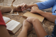 holding hands in prayer at a Bible study