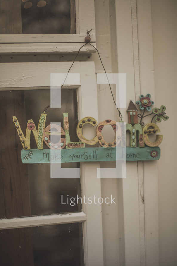 A welcome sign hanging from a window