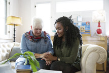 Mature woman and young woman praying together in a home.