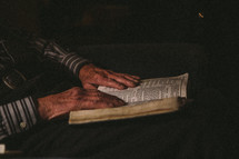 an elderly man reading a Bible in his lap