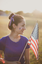 A young woman with USA face paint holding an American flag