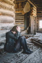 A girl sits with head in hands in an abandoned log house.