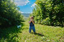 a toddler girl biting an apple