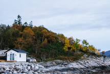 a cabin on a rocky shore in fall