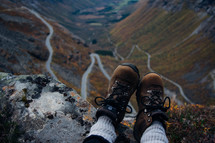 feet in boots hanging off a mountainside