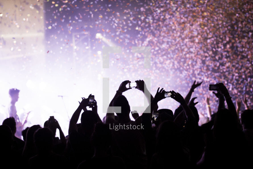 Silhouette of audience at a concert with raised smartphones and confetti in the air.