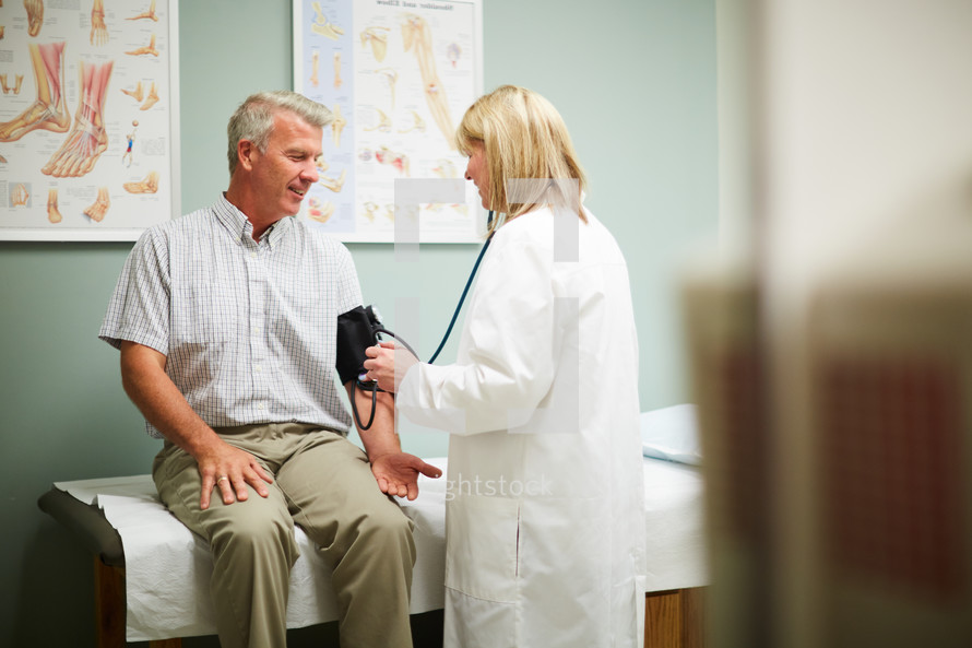 a man at the doctor's office being checked by a woman doctor