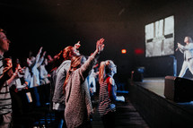 audience with raised hands in front of a stage