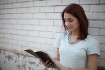 a young woman reading a Bible standing in front of a white wall