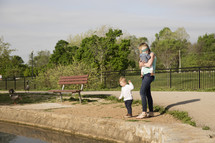 a mother and her kids feeding the ducks at a park