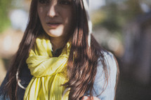 A young woman wearing a yellow scarf