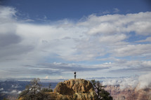 man standing on a peak surrounded by canyons