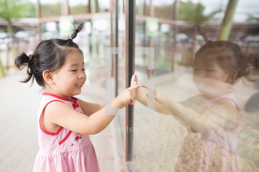 toddler looking at her reflection in a window