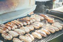 Hotdogs cooking on an outdoor barbecue grill.