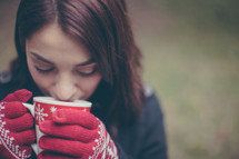 A young woman wearing red gloves drinks hot chocolate from a Christmas cup.