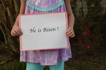 A little girl holding a He is Risen sign