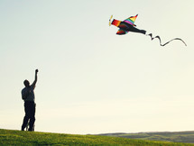 man flying an airplane kite
