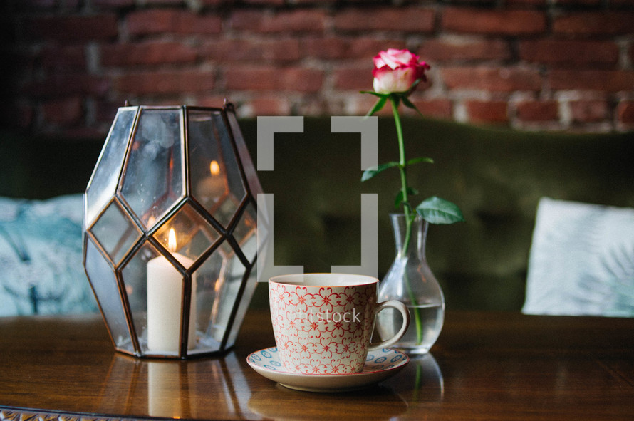 candle in a lantern and rose in a vase