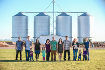family standing on a farm in front of silos