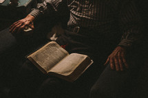 a man reading a Bible on his lap