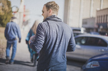 A young man walking down the sidewalk