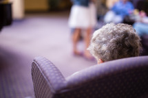 elderly woman sitting in a chair in a nursing home