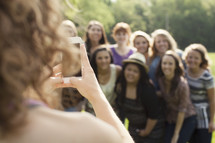 Teenage girl taking a picture of a group of young teen women.