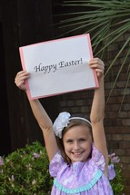 A little girl holding up a Happy Easter sign