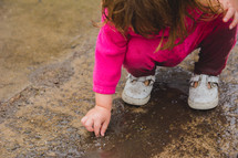a toddler playing in mud