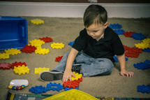 A little boy playing with plastic blocks.