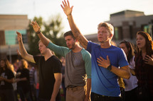 group of people with their hands raised praising God