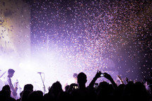 Silhouette of audience at a concert with confetti in the air.