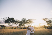 husband and wife walking through tall grass at sunset