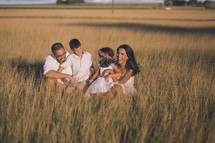 a family in tall grass at sunset