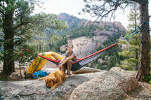 a woman camping sitting in a hammock next to her golden retriever