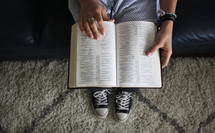 teen girl sitting on a couch reading a Bible