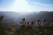 youth sitting on a mountain top under sunlight