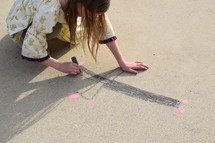 a girl child drawing a cross in sidewalk chalk