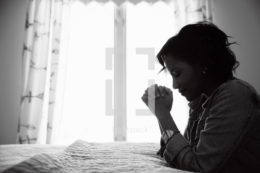 An African American woman kneeling in prayer beside her bed