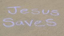 the words Jesus saves in sidewalk chalk