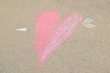 cupid's arrow through a heart in sidewalk chalk