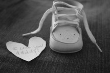 I love you daddy notes on a paper heart and an infant shoe