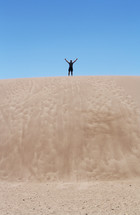 arms raised standing on sand dunes