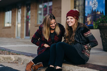 young women in winter attire sitting on a curb talking