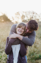a young couple hugging in a field of tall grass